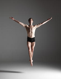 Young attractive modern ballet dancer jumping on white