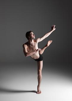 La giovane attraente moderna ballerina sul muro bianco