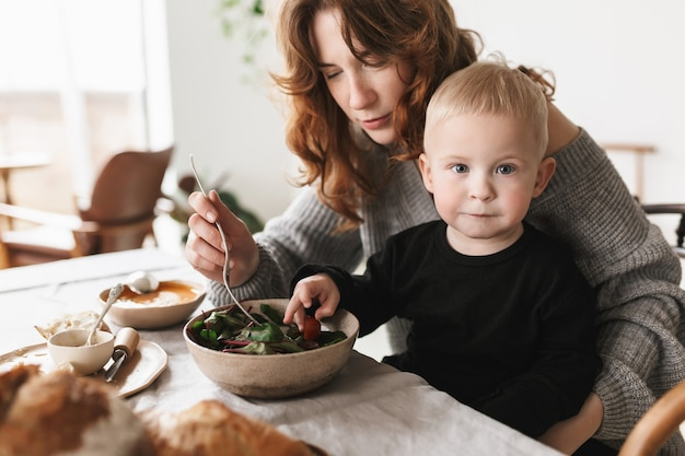Young attractive mom with red hair in knitted sweater sitting at the table, thoughtfully feeding her little son that dreamily
