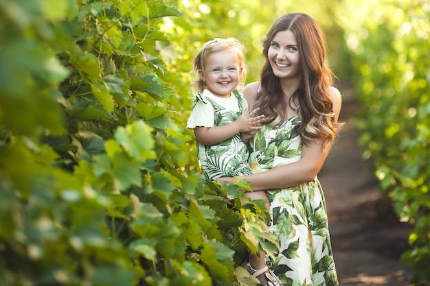若い魅力的な母親と屋外の彼女の小さな女の赤ちゃん。きれいな家族