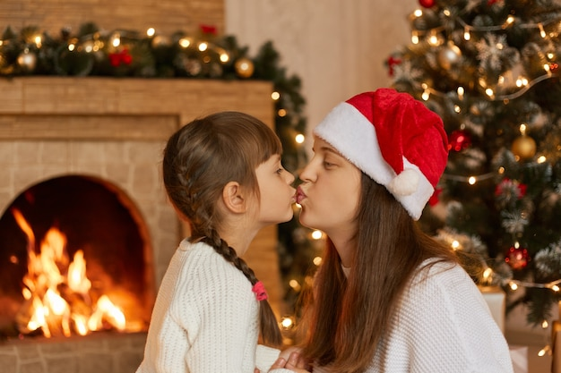 Young attractive mother and daughter posing in living room near xmas tree and fireplace