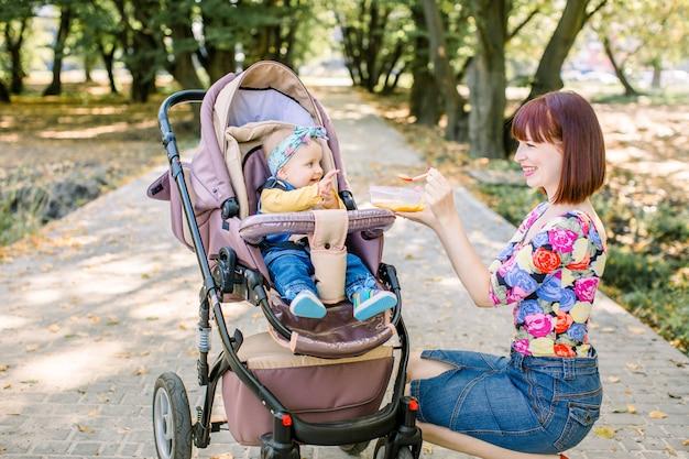 若い魅力的な母親が彼女のかわいい赤ちゃんの女の子に餌をやる、彼女の最初の固形食品、ベビーカーキャリッジに座っていると笑みを浮かべてポーズをとるプラスチックスプーンでニンジンから純粋な健康野菜を与える