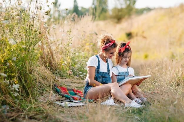 若い魅力的な母親は、夏の公園で娘の絵を教えています。学齢期の子供たちのコンセプトのための野外活動