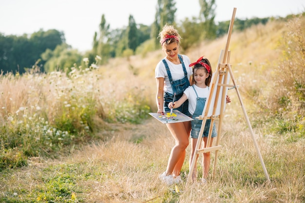 Young attractive mother teaches daughter painting in summer park. outdoors activity for school age children concept