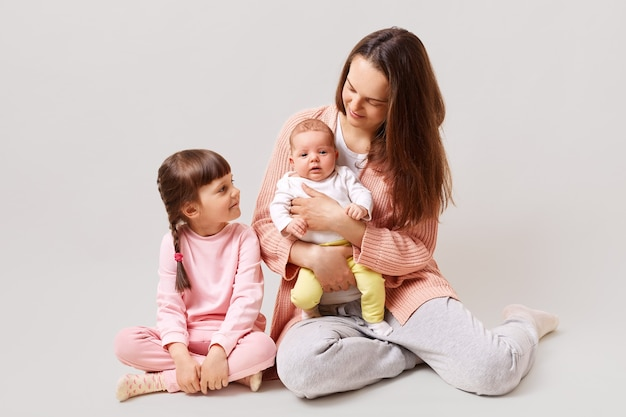 Young attractive mother two daughters sitting on floor