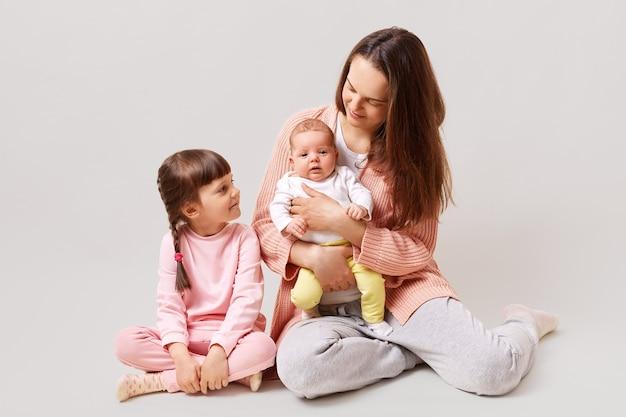 바닥에 앉아 젊은 매력적인 어머니 두 딸