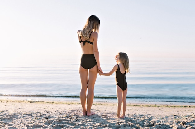 Young attractive mother with little beautiful daughter dressed in black swim suits on the summer beach