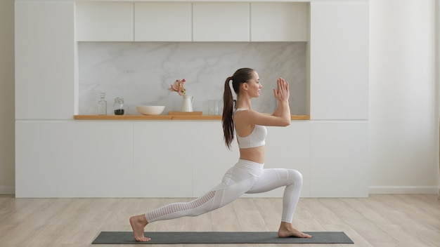 Young attractive multi ethnical woman wearing white sportswear pants and top doing stretching yoga exercises on fitness mat in living room healthcare and exercise mental therapy at home concept