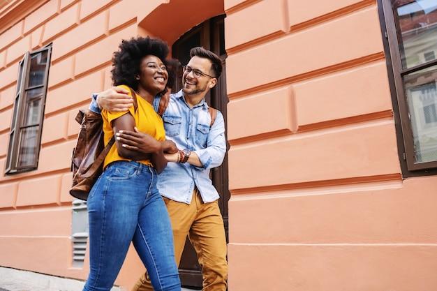 Молодая привлекательная пара мультикультурного обниматься и гулять по улице.