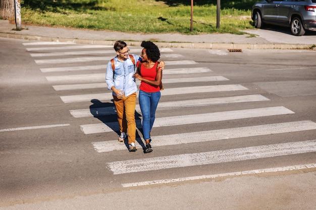 Молодые привлекательные многокультурные счастливые битник пары обнимаются и пересекают улицу.