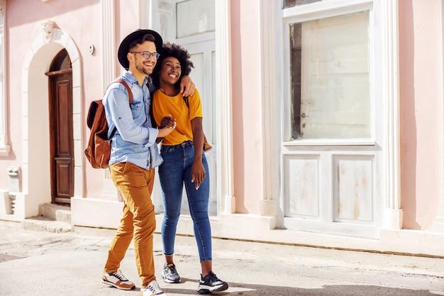 Молодая привлекательная многорасовая влюбленная пара гуляет на открытом воздухе и наслаждается прекрасным солнечным днем.