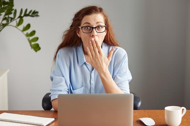Молодой привлекательный офисный работник смотрит с удивлением