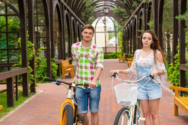 공원의 아치 밑의 통로에서 자유 시간을 보내는 자전거와 함께 젊고 매력적인 쌍
