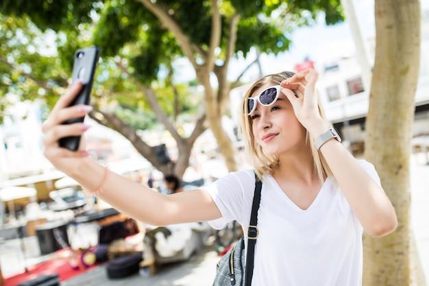 若い魅力的な遊び心のある観光客の女性が外の電話で自分撮りを作っています