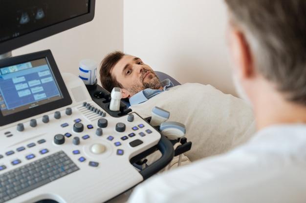 젊은 매력적인 유쾌한 남자가 의료 침대에 누워 과정을 쳐다보기 전에 의사의 지시를 듣고