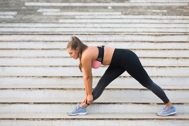 Young attractive plus size woman in sporty top and leggings stretching on stairs while spending time outdoor