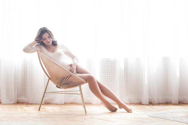 自宅で若い魅力的な妊婦。期待する女性の肖像画をクローズアップ。