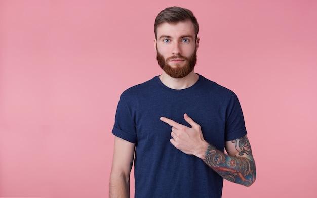 Молодой привлекательный рыжебородый парень, одетый в синюю футболку, смотрит в камеру со спокойным лицом. указывая пальцем на темп копирования на левой стороне, изолированной на розовом фоне.