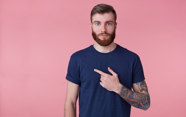 Young attractive red-bearded guy, wearing a blue t-shirt, looking at the camera with a calm face . pointing finger at copys pace at the left side isolated over pink background.