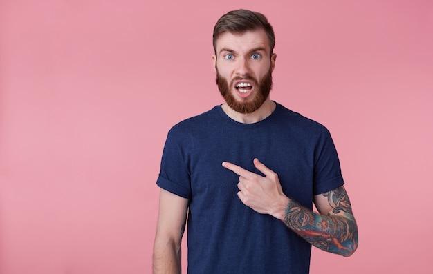 Молодой привлекательный рыжебородый с голубыми глазами выглядит возмущенным, одетый в синюю футболку, хмурится с широко открытым ртом, указывая пальцем в темпе копий слева, изолированном на розовом фоне.
