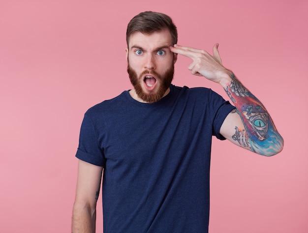 Il giovane attraente ragazzo dalla barba rossa con gli occhi azzurri sembra indignato, indossa una maglietta blu, aggrotta la fronte con la bocca spalancata, ha sentito notizie incredibili e mostra colpi alla testa, isolati su sfondo rosa.