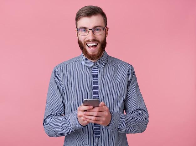 Il giovane uomo attraente con la barba rossa con gli occhiali e una camicia a righe sorride ampiamente, tiene in mano un telefono e gode di un fantastico wi fay, si trova su sfondo rosa.