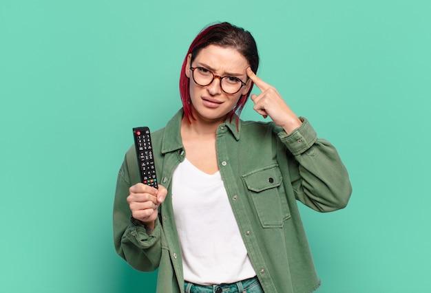 Молодая привлекательная женщина с рыжими волосами чувствует себя смущенной и озадаченной, показывая, что вы сумасшедший, сумасшедший или в своем уме, и держит пульт от телевизора