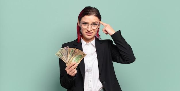 Молодая привлекательная женщина с рыжими волосами чувствует себя смущенной и озадаченной, показывая, что вы сумасшедшие, сумасшедшие или сошли с ума. концепция денег