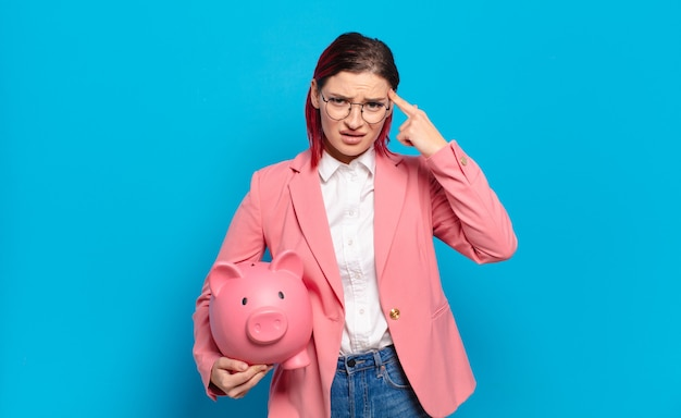 Young attractive red hair woman feeling confused and puzzled holding a piggy bank Premium Photo