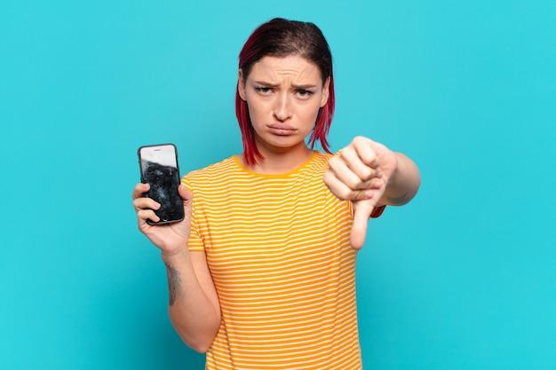 Молодая привлекательная женщина с рыжими волосами чувствует себя раздраженной, сердитой, раздраженной, разочарованной или недовольной, показывая большие пальцы вниз с серьезным взглядом и показывая свою камеру