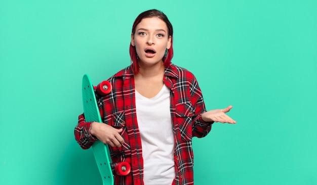 若い魅力的な赤い髪の女性は、ストレスと恐怖の表情で、スケートボードを持って、非常にショックを受け、驚き、不安とパニックを感じています