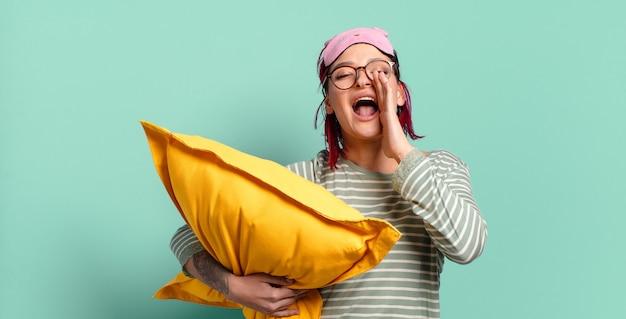 若い魅力的な赤い髪の女性は、幸せで、興奮して、前向きに感じ、口の横に手を置いて大きな叫び声を上げ、パジャマを着て叫びます。