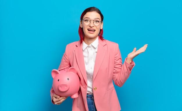 Молодая привлекательная женщина с рыжими волосами чувствует себя счастливой, взволнованной, удивленной или шокированной, улыбается и удивляется чему-то невероятному. юмористическая бизнес-концепция.