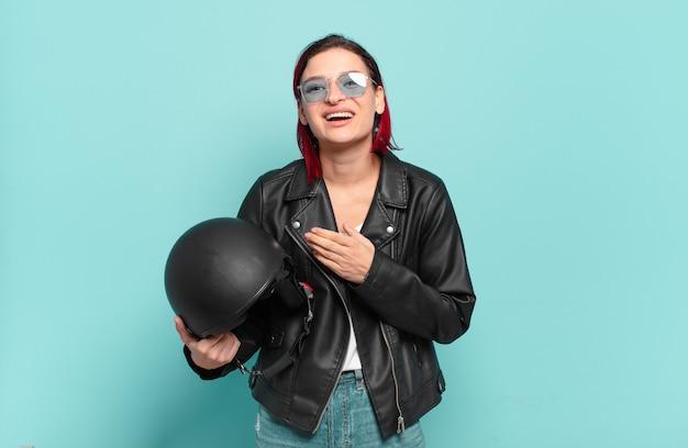 Молодая привлекательная женщина с рыжими волосами чувствует себя счастливой, позитивной и успешной, мотивированной, когда сталкивается с проблемой или празднует хорошие результаты. концепция мотоциклистов