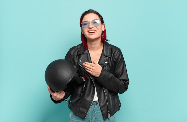 Young attractive red hair woman feeling happy, positive and successful, motivated when facing a challenge or celebrating good results. motorbike rider concept