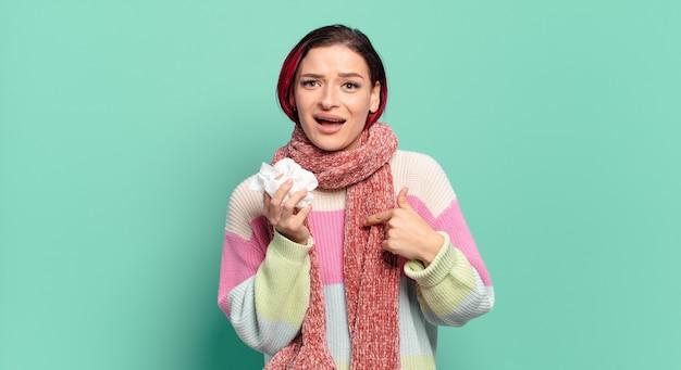 若い魅力的な赤毛の女性は、幸せ、驚き、誇りを感じ、興奮して驚いた表情のインフルエンザのコンセプトで自分を指している