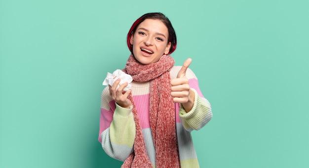 독감 개념을 엄지 손가락으로 긍정적으로 웃고, 자랑스럽고 평온한 자신감과 행복을 느끼는 젊은 매력적인 빨간 머리 여자