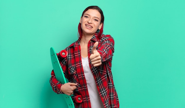 Young attractive red hair woman feeling proud, carefree, confident and happy, smiling positively with thumbs up and holding a skate board
