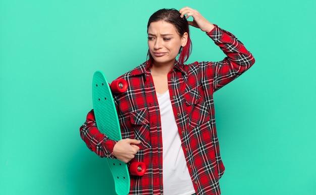 Молодая привлекательная женщина с рыжими волосами чувствует себя озадаченной и смущенной, почесывает голову, смотрит в сторону и держит скейтборд