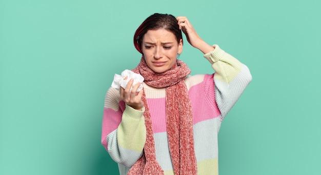 젊은 매력적인 빨간 머리 여성은 어리둥절하고 혼란스러워서 머리를 긁적이며 측면 독감 개념을 바라보고 있습니다.