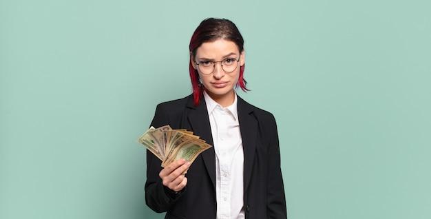 Молодая привлекательная женщина с рыжими волосами чувствует себя грустной, расстроенной или сердитой и смотрит в сторону с отрицательным отношением, хмурясь в знак несогласия. концепция денег
