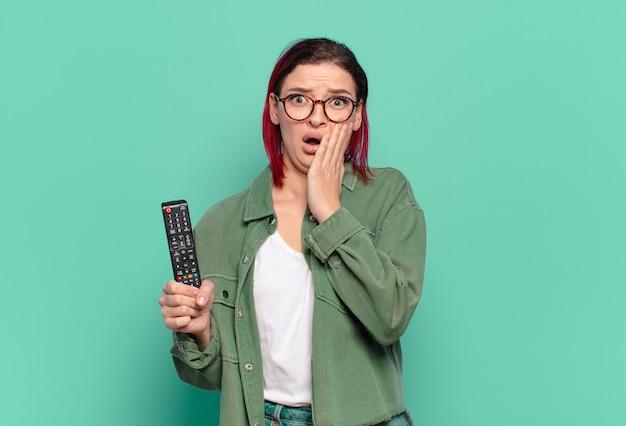 若い魅力的な赤い髪の女性は、ショックを受けて怖がっていて、開いた口と頬に手を当てて恐怖を感じ、テレビのリモコンを持っています