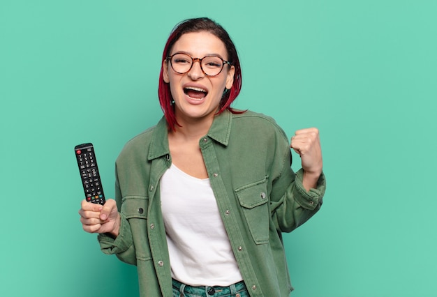 Young attractive red hair woman feeling shocked, excited and happy, laughing and celebrating success, saying wow! and holding a tv remote control