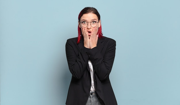Young attractive red hair woman feeling shocked and scared, looking terrified with open mouth and hands on cheeks
