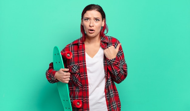 Young attractive red hair woman looking astonished in disbelief, pointing at object on the side and saying wow, unbelievable and holding a skate board