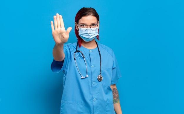 Молодая привлекательная женщина с красными волосами выглядит серьезной, суровой, недовольной и сердитой, показывая открытую ладонь, делая стоп-жест. концепция больничной медсестры