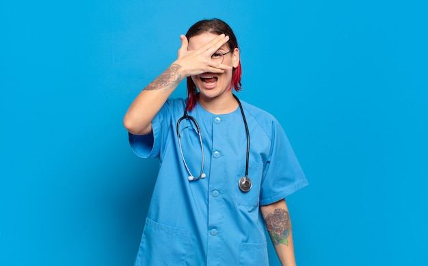 Young attractive red hair woman looking shocked, scared or terrified, covering face with hand and peeking between fingers. hospital nurse concept