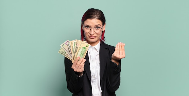 Young attractive red hair woman making capice or money gesture, telling you to pay your debts!. money concept
