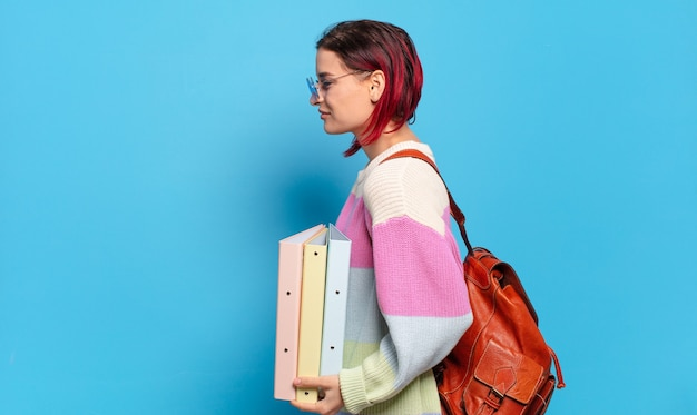Молодая привлекательная женщина с красными волосами на виде профиля, желающая скопировать пространство впереди, думать, воображать или мечтать. концепция студента университета