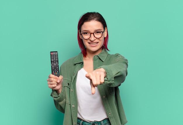 Молодая привлекательная женщина с рыжими волосами, указывая на камеру с довольной, уверенной, дружелюбной улыбкой, выбирает вас и держит пульт от телевизора